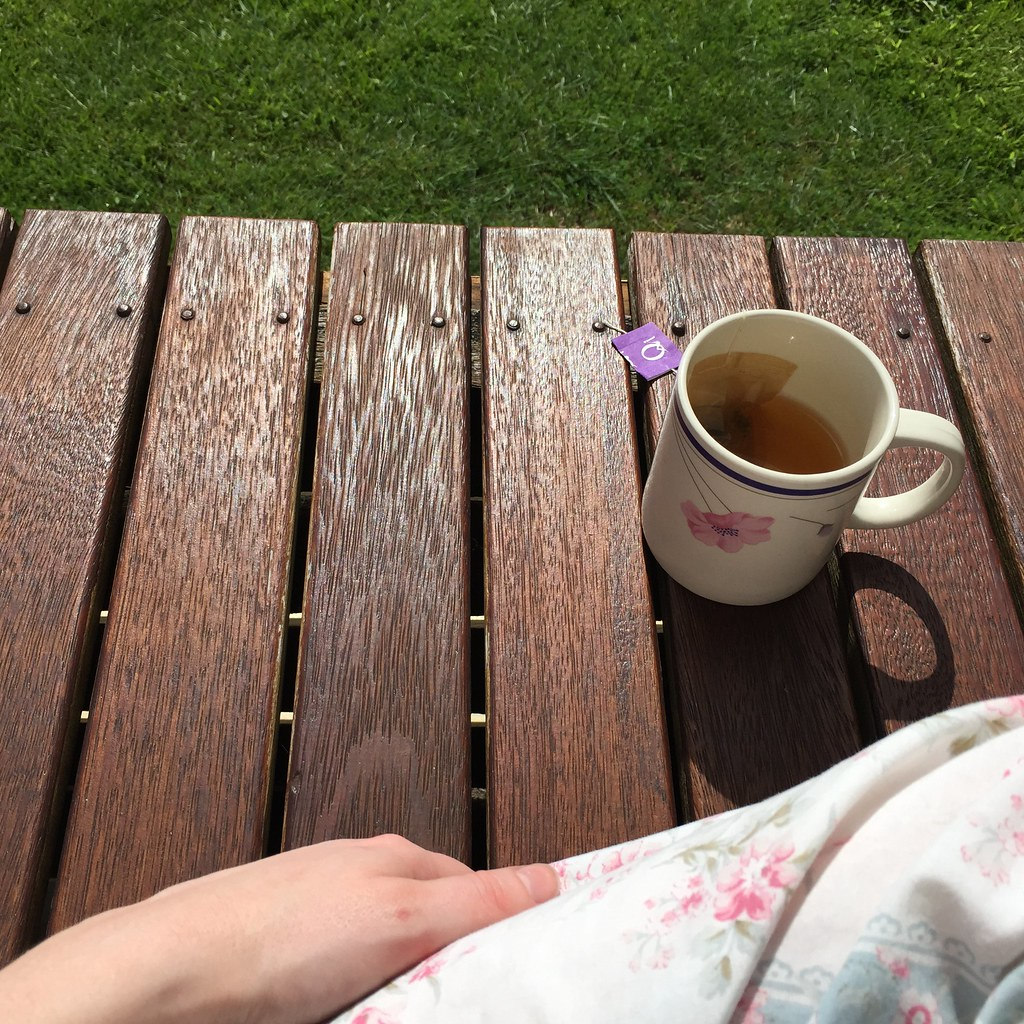 a cup of tea in the sunshine, looking out from the deck at the farm