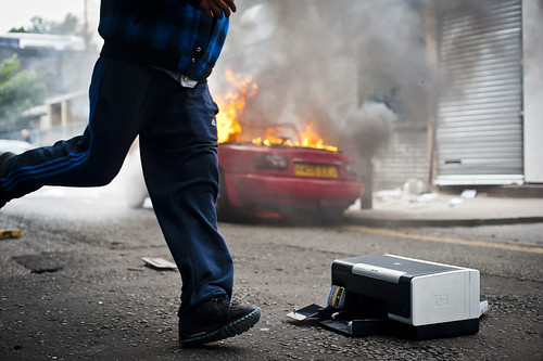 Man running past a burnt car and a looted printer | by ze farinha