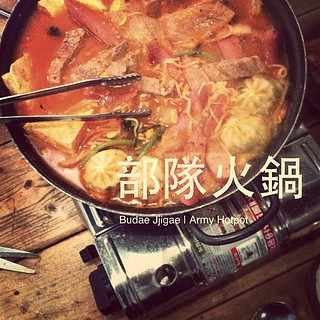 "部隊火鍋, Budae Jjigae, Army Hotpot: Budae jjigae (Korean pronunciation: [pudɛ tɕ͈iɡɛ]; lit. ""army base stew"") is a type of jjigae (a thick Korean soup similar to a Western stew). Soon after the Korean War, meat was scarce in Seoul, South Korea. Some people m 