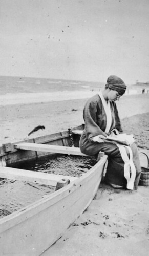 Woman sitting on a beached boat reading a book | by State Library of Queensland, Australia