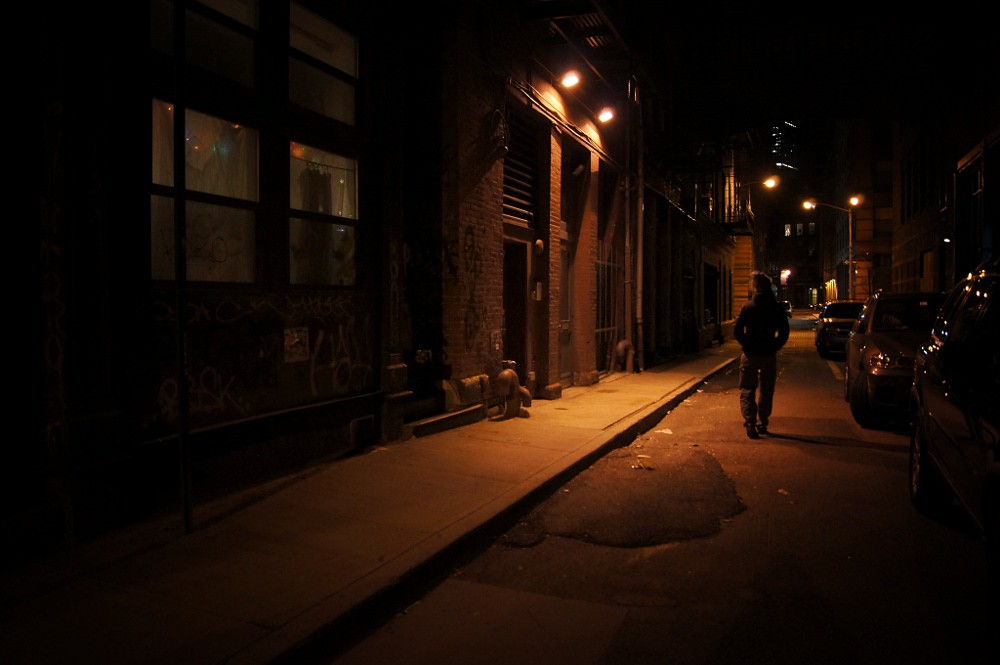 Are man walking down the street at night