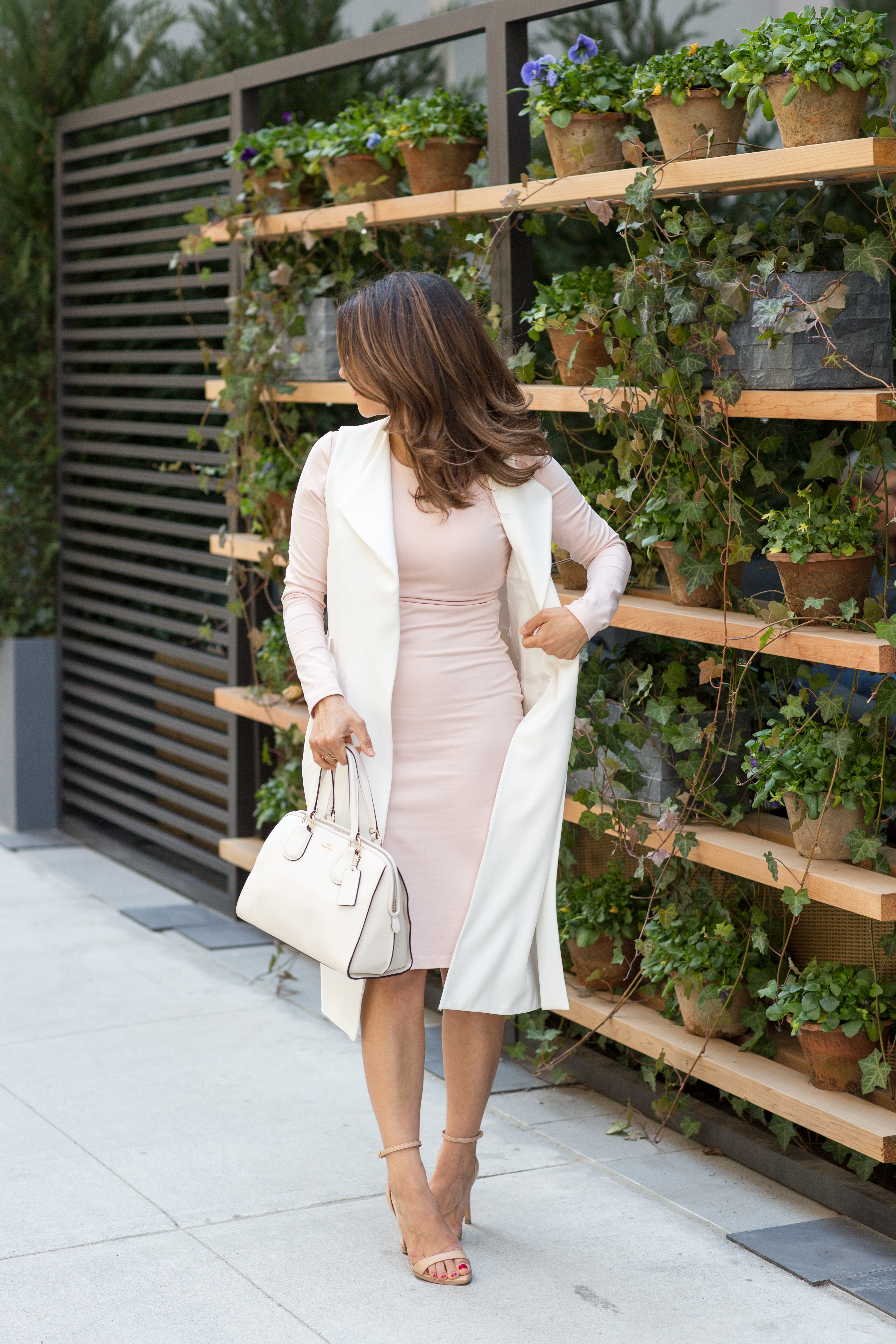 workwear outfit idea for spring wearing blush pink dress, white vest and nude heels