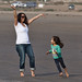 Running circles on the beach, young female child circles her mother who is holding her welcoming arms out.