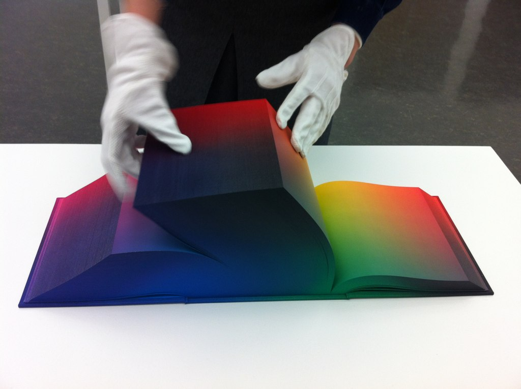 An image of a person's hands, turning pages of a book that is only a color spectrum, printed on its pages.