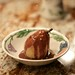 poached pear with chocolate sauce and toffee bits