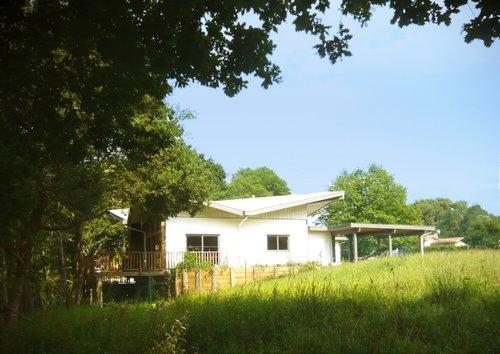 Une maison bois originale avec son toit papillon aboxia for Maison bois originale