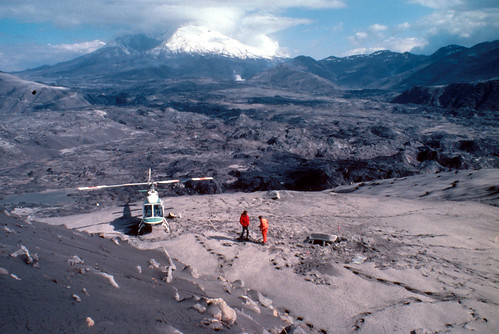 Image shows a hollowed-out, snowcapped Mount St. Helens brooding in the distance. The North Fork Toutle River valley is visible, covered in hummocks from the debris avalanche and mud from the lahars. In the foreground is an ash-covered slope spilling down to a flat gray-brown area. The hood of a car is just visible, buried in the volcanic deposits. A helicopter is parked nearby. Two men in bright red jumpsuits stand near the car, staring down at the deposits.