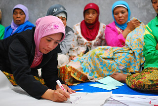 Women at a community meeting discuss the reconstruction of their village | by World Bank Photo Collection