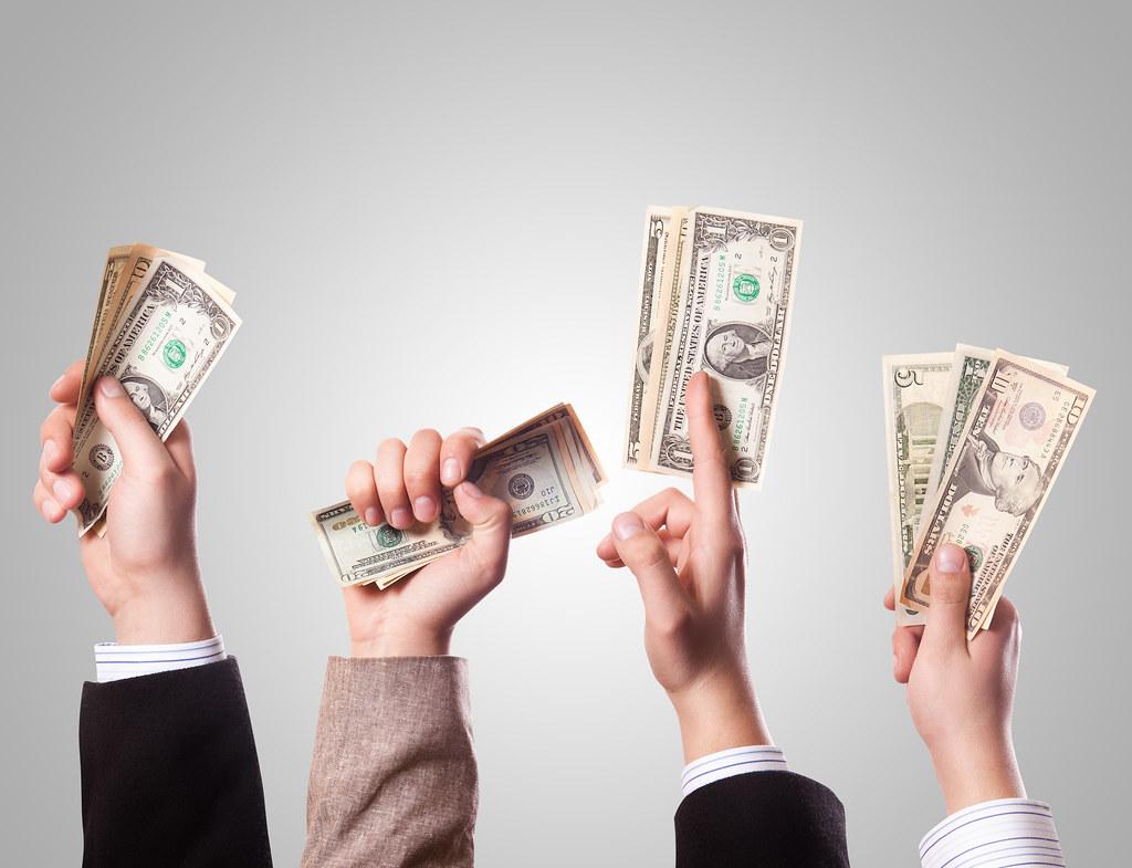 Immagine che mostra 4 mani levate verso l'alto che stringono banconote - Raccolta Fondi per l'organo a canne Carmine Maggiore