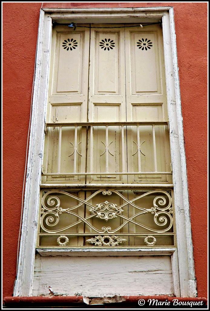 Porte fen tre blanche avec volets ajour s et ornements en for Porte fenetre in english