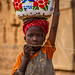 portrait of a little girl with a pot on his head  in front of  great mud mosque in the bani, in the tribal region of the Sahel, northern Burkina Faso