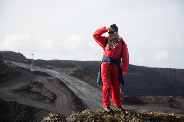 woman protestor standing on the edge of a coal mine