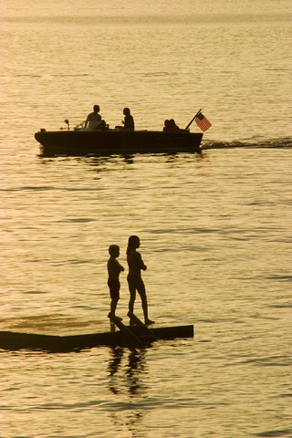 Boating and swimming. Silhouettes in the sunset on a lake. | by ghoffman15