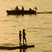 Boating and swimming. Silhouettes in the sunset on a lake.