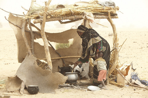 Etta Brahim Senussi outside her home preparing food in her kitchen with her child Mohamed Ali. | by oxfamireland
