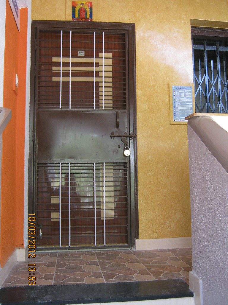 Decorative main door with m s safety door of a flat in san for Decorative main door designs