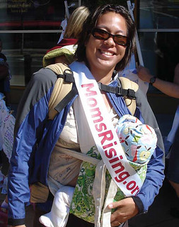 This mom wears her baby along with a MomsRising sash to show her support for equal pay. | by momsrising