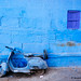 Old Vespa motorbike parked in front of a blue painted wall. Jodhpur, Rajasthan, India