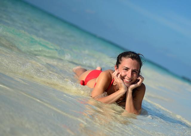 Diana sonriente tumbada en la orilla de la playa de nuestra isla desierta en Odagalla