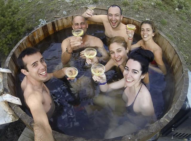 En el hot tub de agua caliente con las copas de sidra en la mano