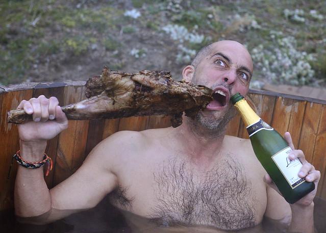 Manolito comiendo cordero dentro del hot tub con una botella de sidra en la otra mano