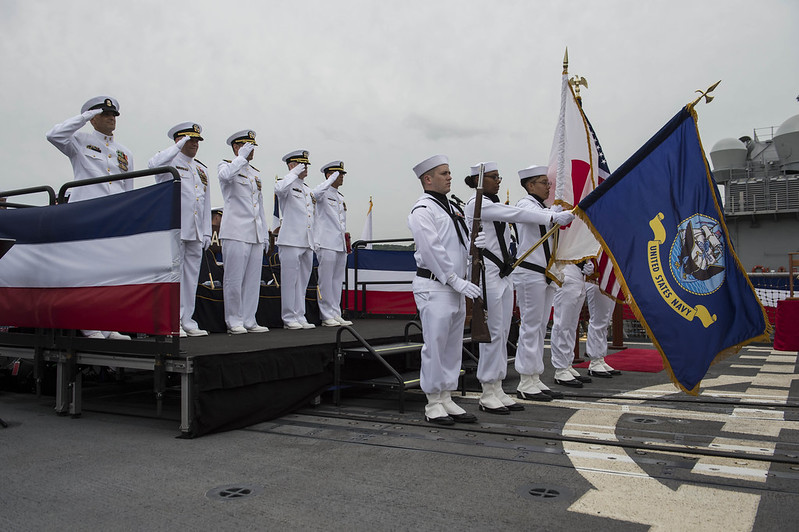 The official party renders honors during the national anthem as part of a change of command ceremony aboard the Ticonderoga-class guided-missile cruiser USS Antietam (CG 54).