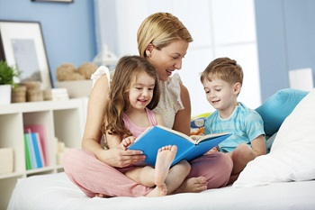Mom reading with her kids at bedtime