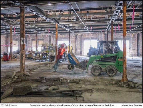 King Street Station Project: 2012-7.25_e9215Demolition worker dumps wheelbarrow of debris into scoop of Bobcat on 2nd floor. | by Seattle Department of Transportation