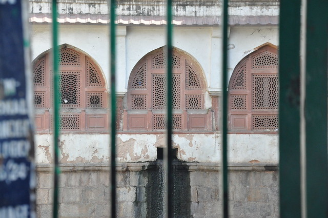 A gate bars the stepwell from the public and is used to regulate the visitors to the water body. Arched, latticed windows are visible across the 'baoli'.