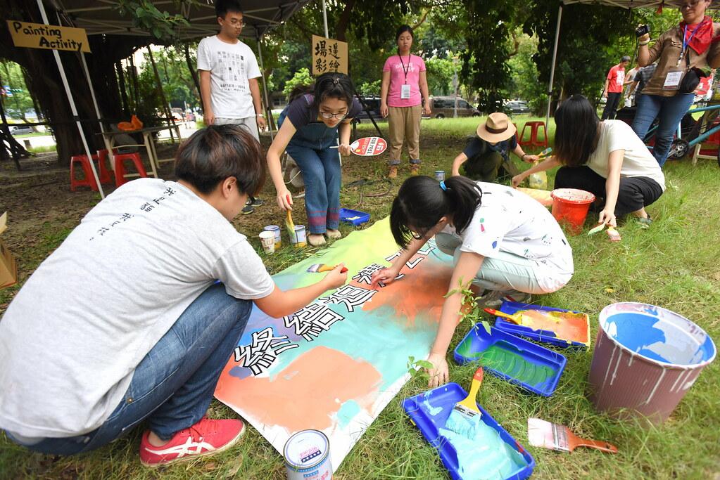 參與者在華光社區舊址草地彩繪「終結迫遷」布條。(攝影:宋小海)