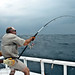 Maldives, fisherman fighting a large Giant Trevally in heavy seas conditions