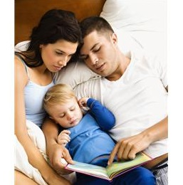 Mom and dad reading to young boy