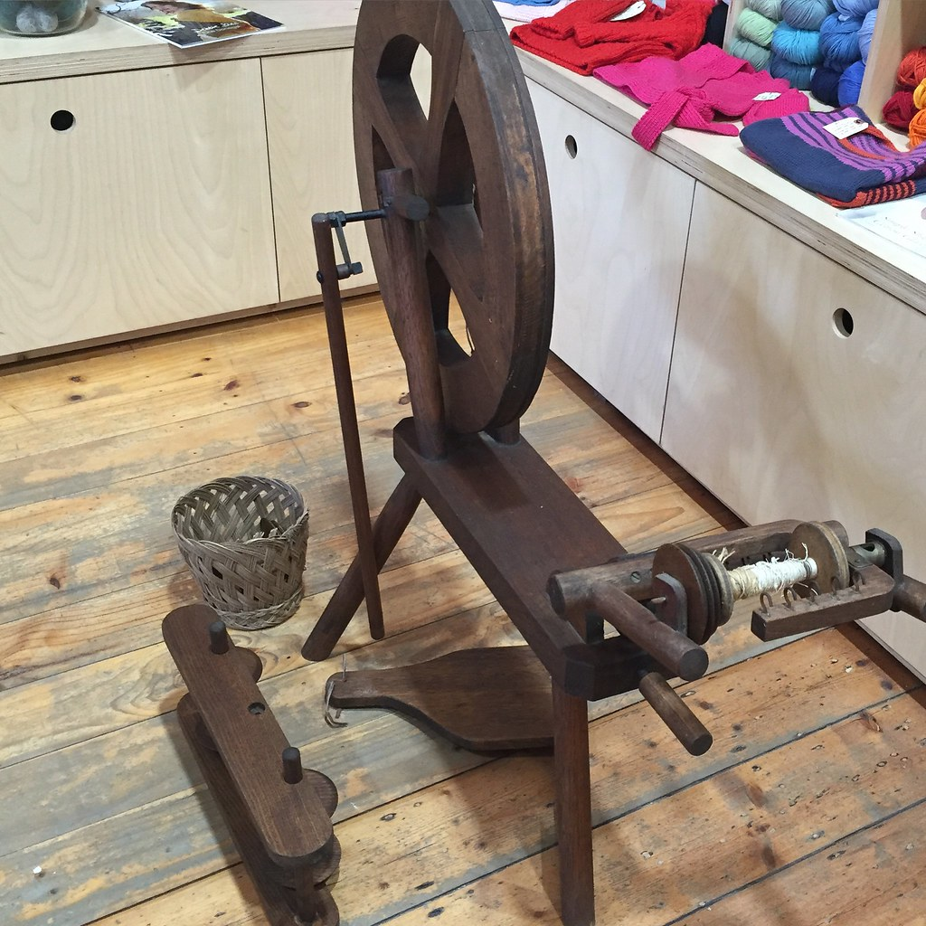 a beautiful, likely handmade, spinning wheel in a dark coloured timber