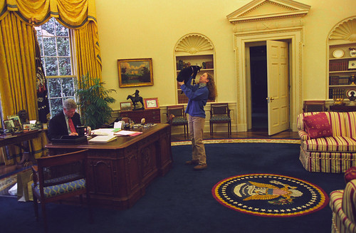 Photograph of Chelsea Clinton Playing with Socks the Cat in the Oval Office While President William Jefferson Clinton Works at his Desk: 12/24/1994 | by The U.S. National Archives