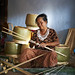 A woman cutting bamboo to weave into baskets