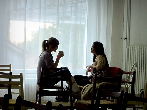 Two people sitting at a small table talking.