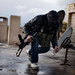 Feb. 10, 2012. A member of the Free Syrian Army takes cover from Syrian Army snipers on the roof of the former police station in al-Qsair