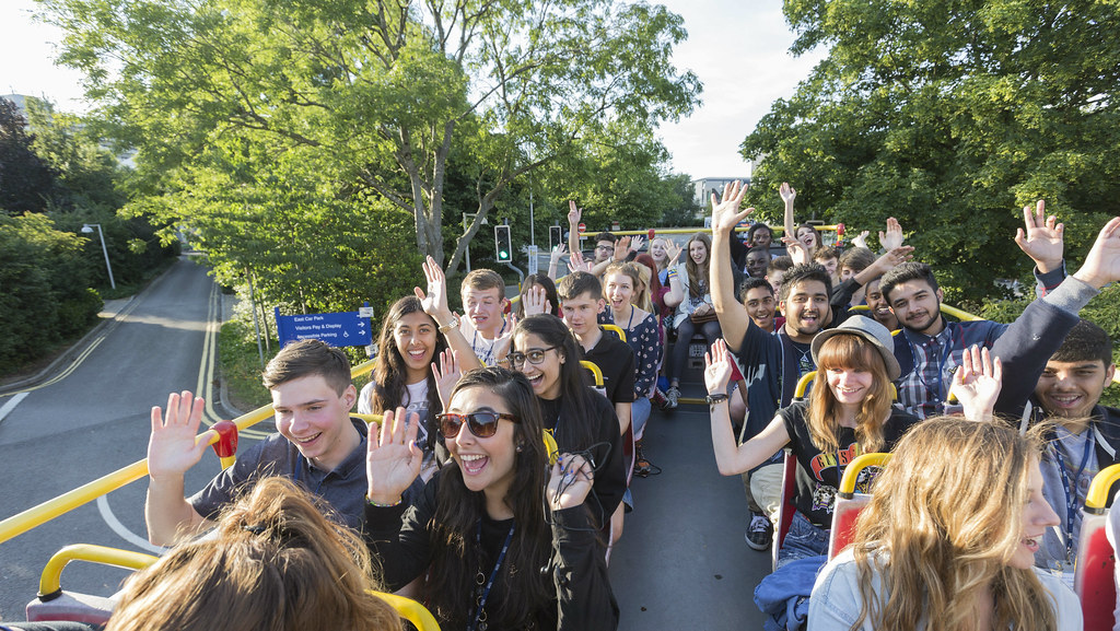 Year 12 Summer School students at the top of a bus as part of a tour of Bath waving for the camera
