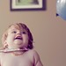 chubby baby laughing at a balloon while wearing a bib as a cape