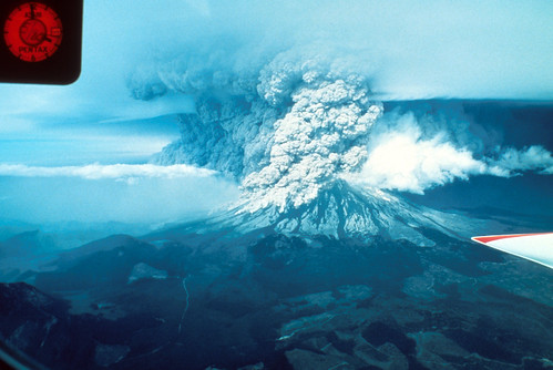 Image shows Mount St. Helens erupting. There is a bit of airplane wing visible at the middle-right. The dark gray Plinian eruption column califlowers up into to sky; part of it is marching out to the north, forming a wall of ash along the ground.