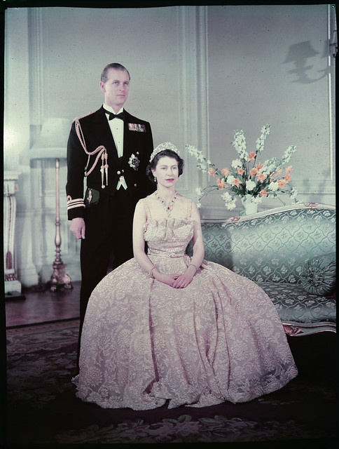 queen elizabeth the second seated in front of prince