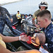 """A Sailor assists in transporting an infant patient into a """"Band-Aid"""" boat."""