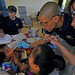 Lt. Chris Chung inspects the mouth of a Vietnamese child.