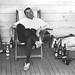 Cricketer sleeping in a deckchair with refreshments and cricket gear awaiting his innings, 1928.