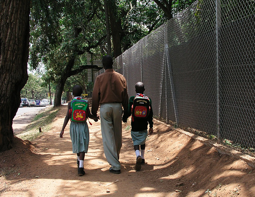A father walks down the street with his children | by World Bank Photo Collection