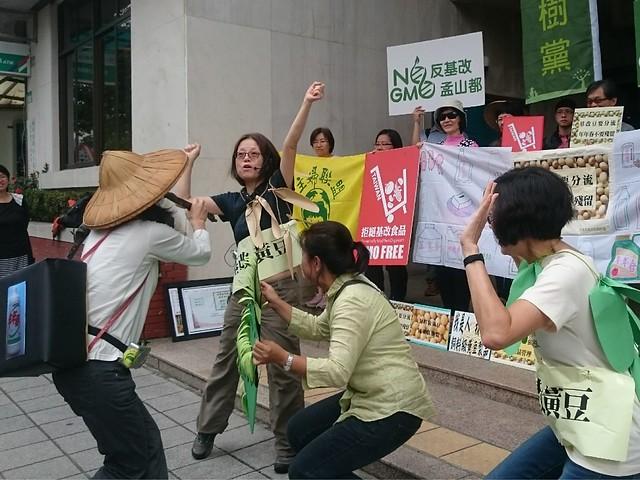 主婦聯盟成員演出行動劇,指出孟山都販賣除草劑「嘉磷塞」與抗藥基改黃豆種子。攝影:賴品瑀。