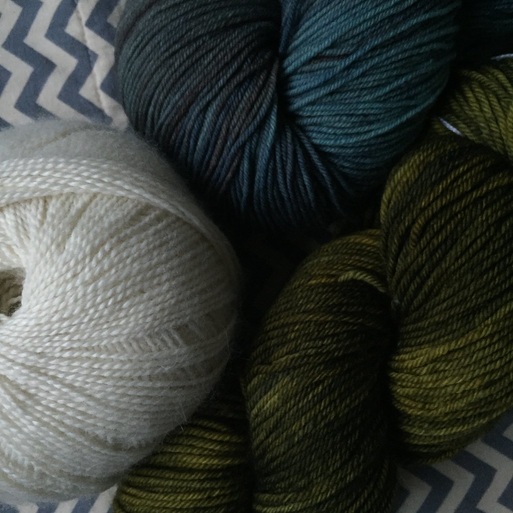 a ball of pure white alpaca/merino/bamboo blended yarn, a skein of dk weight yarn in olive greens and a skein of sock yarn in moody greys and blues