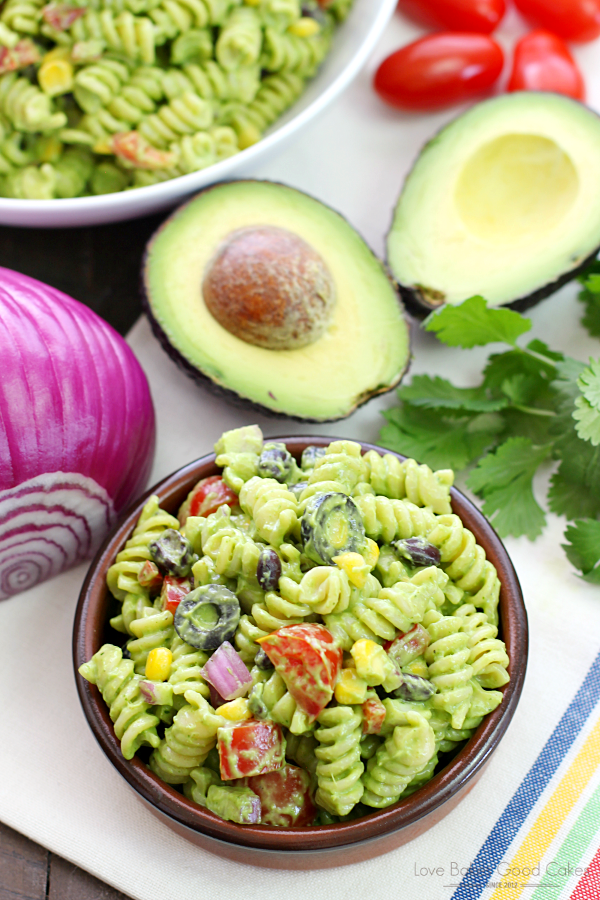 Avocado-Cilantro Pasta Salad in a brown bowl with an avocado and a red onion.