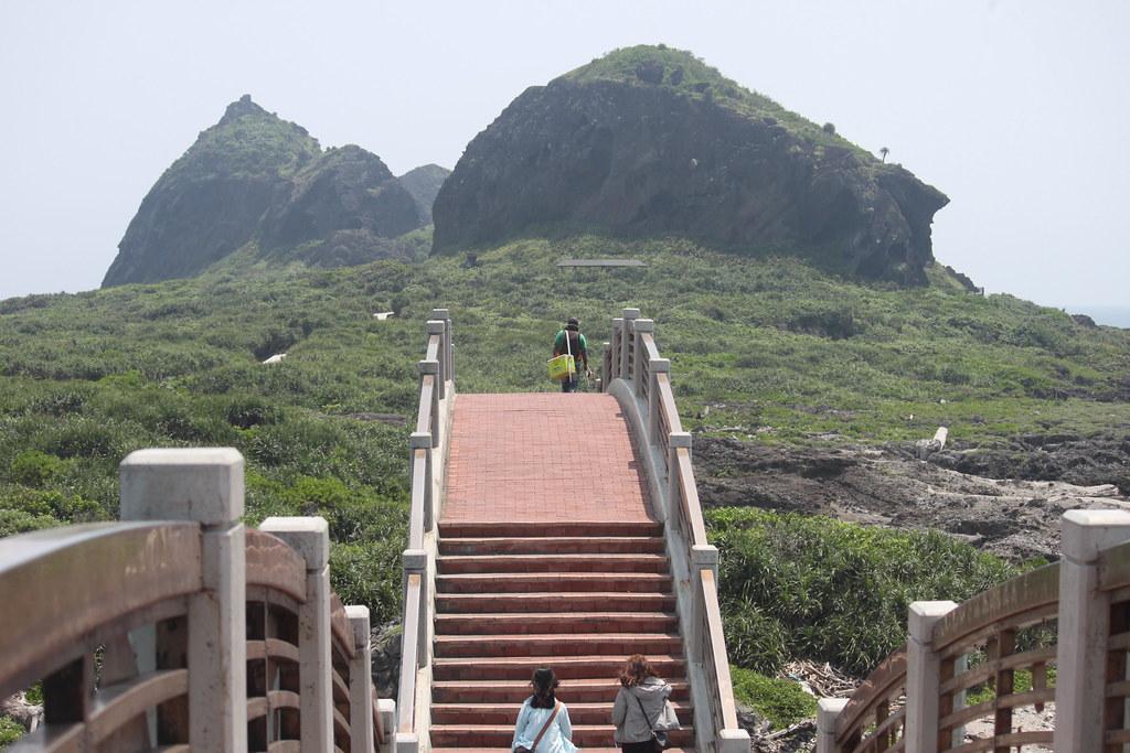 釣客與遊客越過拱橋,前往離岸島的背影,民國70年代前,沒有這座橋,部落居民都是越過潮間帶登島,橋出現後,橋墩侵佔了居民過海的路線,綿長的樓梯讓人失去跨越的動力,因為一切看起來都跟以前不一樣了,部落的人這麼說著...