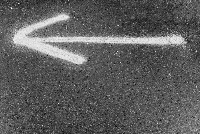 black and white arrow pointing left